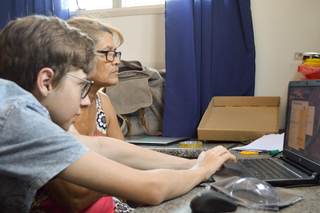 A young Projects Abroad volunteer teaches an adult woman how to use a computer program during his IT teaching internship in Ghana.